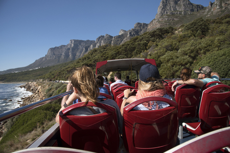CAMPS BAY RESORT WESTERN CAPE SOUTH AFRICA  - Tourists on a tour bus passing the Twelve Apostles mountain range near Cape Town