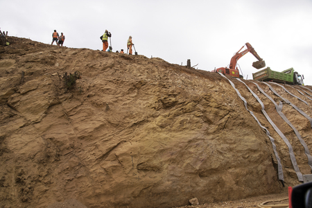 retain: N2 HIGHWAY WESTERN CAPE SOUTH AFRICA - APRIL 2016 - Contractors using straps to retain a earth and rock cutting on the N2 Highway near Elgin in the Weatern Cape