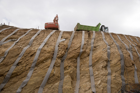 land slide: N2 HIGHWAY WESTERN CAPE SOUTH AFRICA - APRIL 2016 - Contractors using straps to retain a earth and rock cutting on the N2 Highway near Elgin in the Weatern Cape