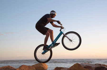 skillfully: THE STRAND WESTERN CAPE SOUTH AFRICA - APRIL 2016 - Amountain bike rider skillfully riding over rocks on the shoreline at The Strand in the Western Cape Editorial