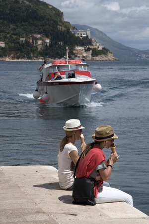 inter: DUBROVNIK HARBOR CROATIA - MAY 2016 - Two young female tourists sitting on the harbor wall in Dubrovnik eating ice cream as an inter island ferry boat approaches