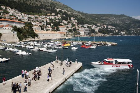 mingle: OLD HARBOR DUBROVNIK CROATIA - MAY 2016 - Tourists mingle at the Old Harbor in Dubrovnik where small ferry boats arrive and depart to outlaying islands Editorial