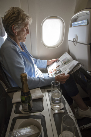 onboard: WOMAN AIRLINE PASSENGER ONBOARD A COMMERCIAL JET - MAY 2016 - An elderly lady passenger seated by an aircraft window reading a magazine