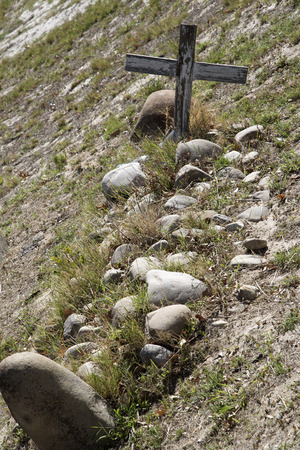 unmarked: WESTERN CAPE SOUTH AFRICA - APRIL 2016 - An old unmarked grave with a wooden cross surrounded with rocks in the Western Cale Southern Africa Editorial