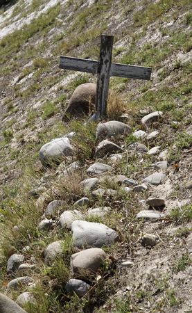 stone tombstone: WESTERN CAPE SOUTH AFRICA - APRIL 2016 - An old unmarked grave with a wooden cross surrounded with rocks in the Western Cale Southern Africa Editorial