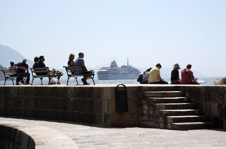 cruis: DUBROVNIK HARBOR CROATIA - MAY 2016 - Tourists to Debrovnik harbor sitting on the harbor wall relaxing in the sunshine