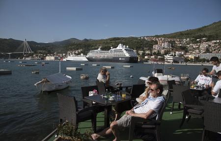 literas: Dubrovnik Croacia - mayo 2016 - El puerto de Gruz y la terminal de cruceros a las afueras de la ciudad de Dubrovnik. Los turistas se relajan en un café de la orilla del agua Editorial