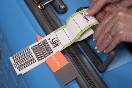 priority: PRIORITY TAG ON A BLUE SUITCASE - MAY 2016 - Airline priority tag being secured to a blue suitcase Editorial