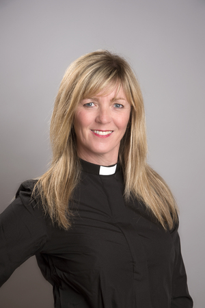 clergy: Portrait of a female clergy wearing a black shirt and dog collar