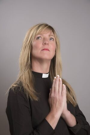 clergy: Portrait of a female clergy wearing a black shirt and dog collar praying