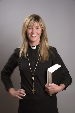 Portrait of a female clergy wearing a black shirt and dog collar