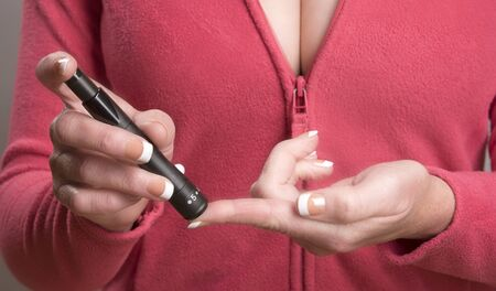 blood glucose meter: Woman using a blood glucose meter to check her blood
