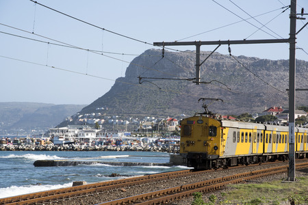 south western: KALK BAY WESTERN CAPE SOUTH AFRICA - APRIL 2016 - The scenic coastal suburban railroad line which runs between Cape Town and Simpns Town seen here passing Kalk Bay Western Cape Southern Africa