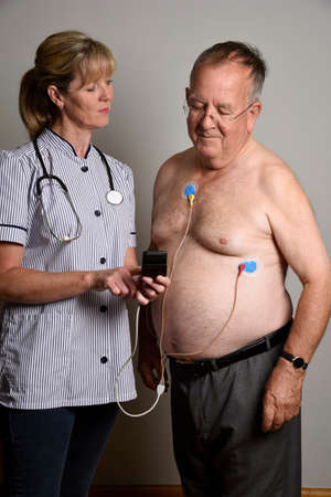 ambulatory: ENGLAND UK - JUNE 2016 - Member of a hospial cardiac measurement team installing a ambulatory ECG monitor to an overweight male patient