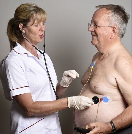 ecg monitoring: ENGLAND UK - JUNE 2016 - Member of a hospial cardiac measurement team installing a ambulatory ECG monitor to an overweight male patient