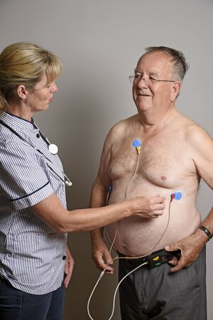 cardiograph: ENGLAND UK - JUNE 2016 - Member of a hospial cardiac measurement team installing a ambulatory ECG monitor to an overweight male patient