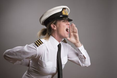 mouthing: OFFICER SHOUTING AN ORDER MAY 2016 - Portrait of a female uniformed officer wearing a uniform cap shouting an order