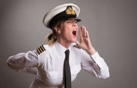 OFFICER SHOUTING AN ORDER MAY 2016 - Portrait of a female uniformed officer wearing a uniform cap shouting an order