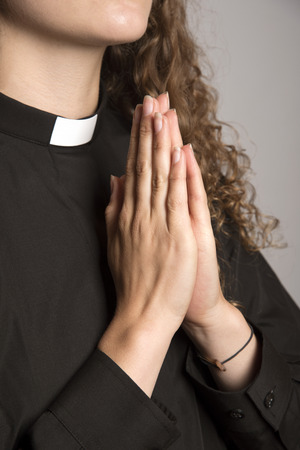 vicar: Hands clapsed together praying Stock Photo