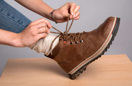 rubber sole: Woman tying the laces on her walking boot