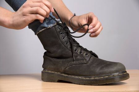 womans: Womans hand lacing up a black leather boot