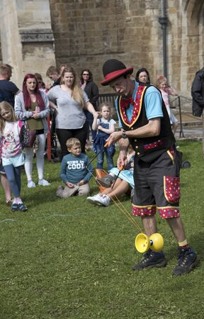 entertainer: WINCHESTER HAT FAIR HAMPSHIRE ENGLAND UK - JULY 2016 - Entertainer amusing adults and children during the annual Hat Fair outside the Winchester Cathedral. Editorial