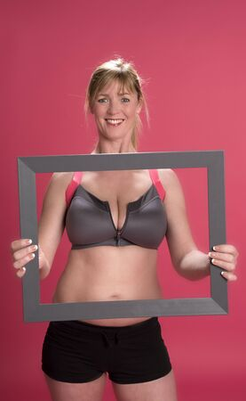 keep fit: Woman in keep fit gear holding a wooden frame