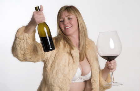 A woman wearing a fur coat holding a bottle and glass of wine Stock Photo