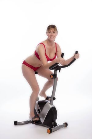mid age: WOMAN RIDING AN EXERCISE BIKE - A mid age woman wearing red underwear riding an exercise bicycle