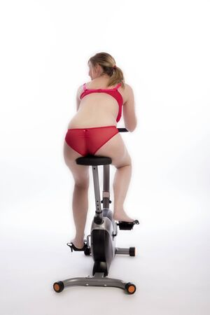 WOMAN RIDING AN EXERCISE BIKE - A mid age woman wearing red underwear riding an exercise bicycle