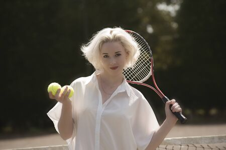 Raquet: PORTRAIT OF A YOUNG TENNIS PLAYER  - A young female tennis player with fair hair holding a raquet and tennis balls Stock Photo