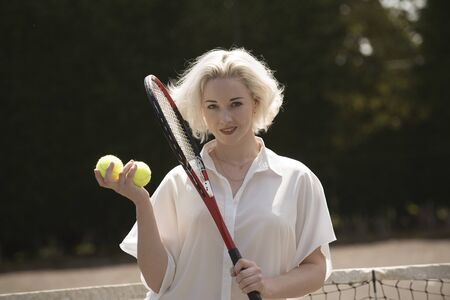 Raquet: A young female tennis player with fair hair holding a raquet and tennis balls Stock Photo