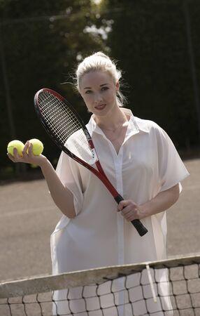 fair hair: PORTRAIT OF A YOUNG TENNIS PLAYER   - A young female tennis player with fair hair holding a raquet and tennis balls