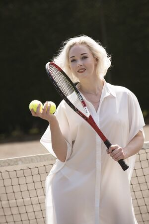 Raquet: PORTRAIT OF A YOUNG TENNIS PLAYER   - A young female tennis player with fair hair holding a raquet and tennis balls