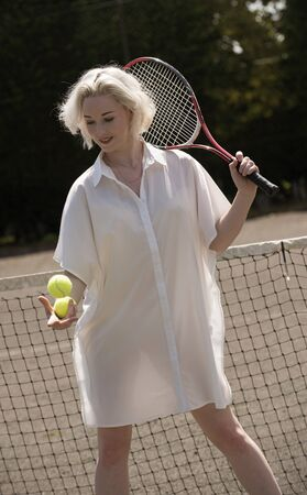 Raquet: PORTRAIT OF A YOUNG TENNIS PLAYER -JULY 2016 - A young female tennis player with fair hair holding a raquet and tennis balls