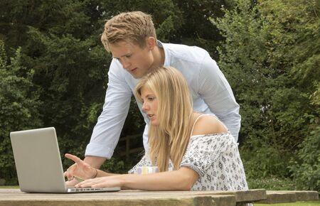 garden table: A teenage couple using a computer on a garden table