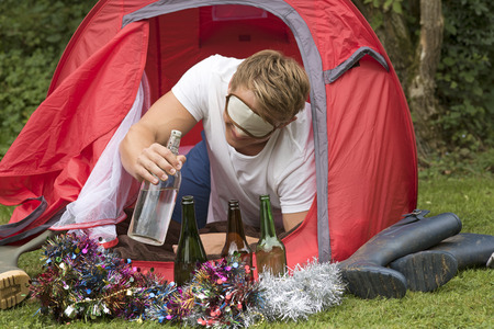 A camper reaches outside his tent for a water bottle