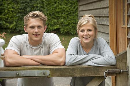 Portrait d'un couple d'adolescents se penchant sur une porte