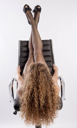 fishnet tights: Woman with long hair and wearing fishnet tights laying on an office chair