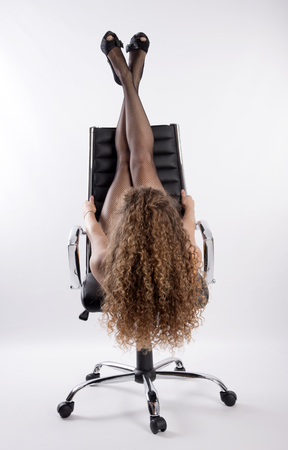 fishnet: Woman with long hair and wearing fishnet tights laying on an office chair