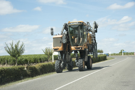 straddle: A Straddle tractor with spraying equipment on a public road. Saint Julian in the Medoc region of France