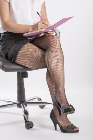 shorthand: Woman wearing fishnet tights and a notebook on her knee