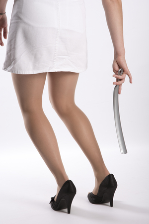 Young woman using a long shoe horn to reach her high heel shoes Stock Photo