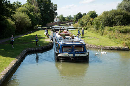A hotel boat underway on the Kennet and Avon canal at Caen Hill close to Devizes Wiltshire England UK