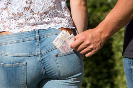 pickpocket: Thief taking money August 2016 - A pickpocket taking money from a girls pocket