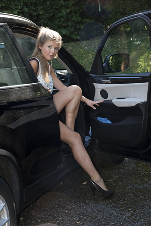 exiting: Young female driver exiting her car Stock Photo