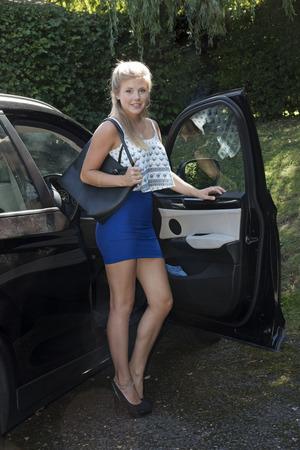 falda corta: Conductor joven mujer en una falda corta que sale de su coche
