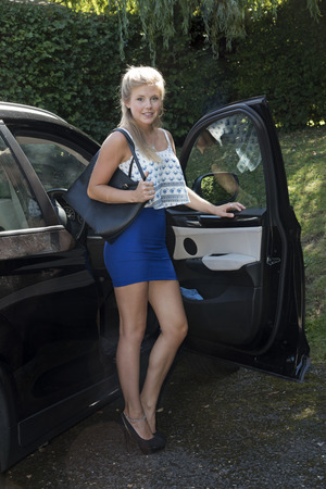 exiting: Young female driver in a short skirt exiting her car Stock Photo