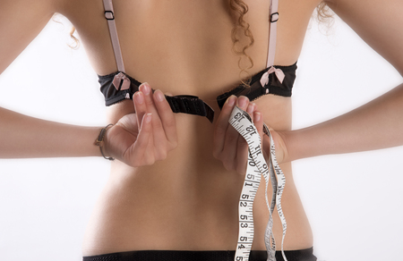 Young woman holding a tape measure and fastening her bra Stock Photo