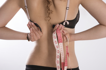 undergarment: Young woman holding a tape measure and fastening her bra Stock Photo